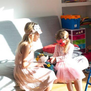 Children playing wearing cat masks