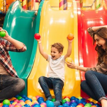 Parents enjoying playing soft play with their child.